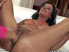 Voracious dirty brunette mommy plays with a huge sex toy on the couch