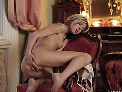 Divine blond amateur sits on the luxurious chair while her hands are busy stroking both her small perky tits and bald unused vagina in peppering solo sex video by 21 Sextury.