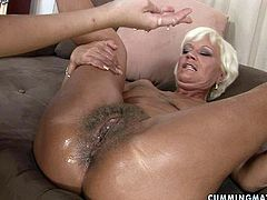 Wanton grey-haired granny lies on her back spreading her legs wide while an insatiable brunette amateur pounds her botomless hairy vagina with a thick end of baseball batt.