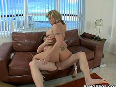 Blonde chick with big boobs sucks a dick sitting on the floor. Then she lies down on the sofa and gets fucked deep in her wet pussy.