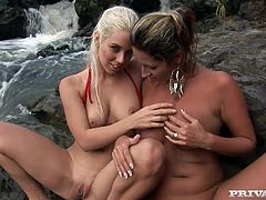 Daria Glower and Nesty take their bikini off and lick each others tits sitting on the rocks in the river. Of course they also lick pussies to make each other cum.