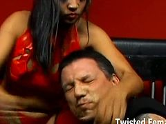 This dominant Asian dressed in latex takes her slave out of his cage and starts torturing him with different objects.