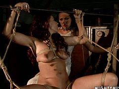 Curvy brunette bombshell gets suspended bandaged before an insatiable domina starts fucking her soaking vagina with a dildo in BDSM sex video by 21 Sextury.
