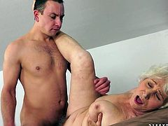 Perverse dude makes out with a shabby grey-haired granny. He nails her silver pussy in missionary style before she starts rubbing his cock between oversized slack tits.