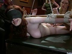 Naughty redhead chick gets tied up and fucked rough in public. She gets her tits twisted with ropes and pussy fucked hard.