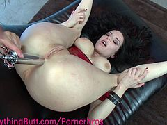 With her legs wide apart, this big titted brunette got her asshole spread with a clamp, then her kinky and naughty lover stuff and stretch it apart with a monster size toy cock while she flick her clit.