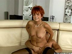 This raunchy granny with red color hair is wearing nothing but black nylon stockings. She gets on top of solid prick of young stud that is half of her age. She jumps passionately in cowgirl sex position.