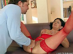 Horn made brunette mature in raunchy red lingerie and fishnet stockings gets her bald pussy tongue fucked by young lover before she inclines to his oversized penis to give it a head.