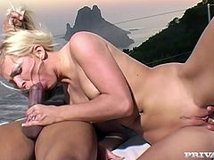 Sweet blonde babe in pink bikini sucks big black cock outdoors. Then she gets her tits and pussy licked. After that she gets fucked hard on a lounge chair.