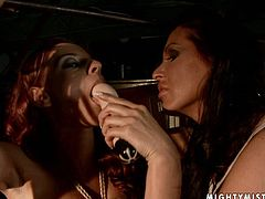 Busty brunette hottie stands on her knees with body and hands bandaged while a rapacious domina forces her suck a slim dildo, which she later uses to drill her moist punani.