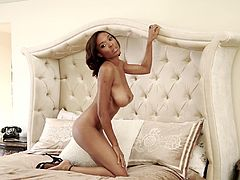 Superb Black Playboy babe takes the clothes off and sits down on a bed. She shows her juicy tits and nice ass.