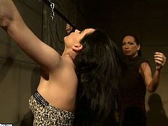 Alluring brunette hottie gets lured by insatiable big lipped domina. She suspends her before she starts choke her with hands and later pinches her hard nipples in BDSM-styled sex video by 21 Sextury.