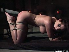 Divine brunette babe gets crucified with a rope while a kinky dude pours hot wax on her naked body before she switches to doggy pose bandaged to get fucked with dildo in BDSM-styled sex video by 21 Sextury.