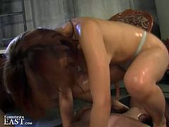 Naughty Japanese femdom dominates submissive lesbian. Nasty asian is covered with oil, she rubs her pussy against her slave's face and fingers her hairy pussy.