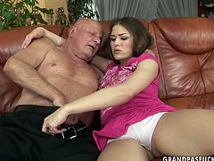 Kinky girl with pretty face is seduced by horny old grandpa. She takes his cock in her mouth sucking it like tasty lollicock.