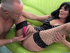 Horn made brunette mature sits on the couch with legs spread aside wearing nothing but black lingerie and fishnet stockings while a perverse daddy tickles her snatch with sex toys.