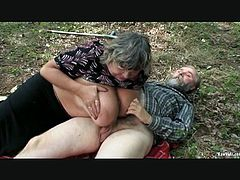 A mature woman is getting her big-ass titties licked and sucked outdoors in the woods by a bearded old man, when a cute and tight redhead teen spots them and can't help but to lift up her skirt and start rubbing her clit and fingering her wet pussy.