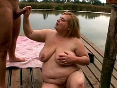 Amateur blonde BBW with big tits and big belly fucking a horny guy near a lake in Oregon. They fuck standing as it's cold outside.