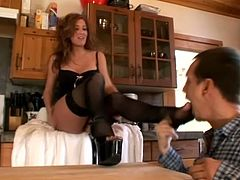 Sexy brown-haired milf Morgan Reigns is getting naughty with some dude in the kitchen. She sucks his cock remarcably well and then pleases the guy with an awesome footjob.