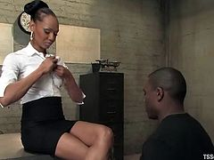 Ebony tranny Foxy is having fun with Jack Hammer indoors. They caress each other and then the dude leans against a desk and gets his ass fucked from behind.