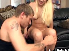 This blonde babe with tiny tits is a little dominant. She has a guy licking her soles and sucking on her toes. Then, she wraps her soft feet around his cock and jerks it.