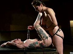 See how the tattooed brunette Krysta Kaos gets her cunt fucked by Bobbi Starr's strapon dildo in this kinky lesbian BDSM video with some torture.