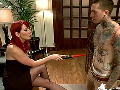 Redhead mistress Maitresse Madeline is playing dirty games with a tattooed dude called Ruckus. She ties his cock and balls around and then kicks his groin and plays with his schlong.