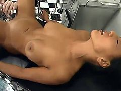Sexy brunette girl lies naked on a hospital chair. She gets her tight pussy toyed with an electric dildo by kinky blonde nurse.