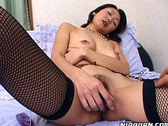 Horn made Japanese MILF in provocative leopard-printed garter belt and black fishnet stockings lies on the bed while a voracious dude pinches her brownish nipples before he turns to her hairy pussy to stimulate it with mini vibrator.