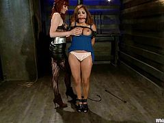 Submissive girl with big boobs gets gagged and tied up by redhead mistress. Later on this babe also gets her pussy toyed with a strap-on and a vibrator.