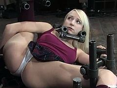 Kinky blonde girl lies on the floor being bonded with BDSM devices. She also gets her pussy drilled with a fucking machine.