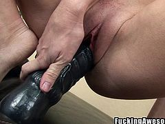 Brandi pulls out her gigantic black dildo. Look at the size of this thing. She manages to get almost the whole thing inside her vagina. Wow. She can take a lot of plastic in her pussy. She is such a dirty whore.