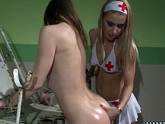 Sexy blonde nurse wearing medical bikini finger fucks pussy of sweet looking brunette patient. She oils up her gorgeous butt and she is going to finger fucks her.
