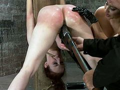 Hot redhead girl gets tied up to a wooden post. After that she gets her ass spanked and pussy stuffed with big dildo by brunette chick.