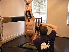 She gets a lot of pain in this BDSM porn video. Honey gets suspended with her mouth gagged and then her master spanks her petite ass.