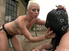 She's blonde, hot and loves to humiliate men. This time the divine bitch Lorelei got her paws on Ivo. She bent him over those tires and made the guy suck her strap on dildo. After she finished fucking his mouth, she fingered his ass hole, preparing his ass, for what's about to come