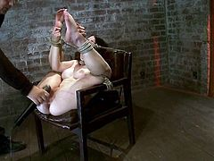 Lovely brunette sits on a chair being hog tied and gagged. Then the master fingers and toys her hot pussy with a vibrator.