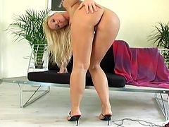 Hot blonde solo babe takes her clothes off. She poses naked and lies down on a couch. She spreads the legs and massages her shaved pussy.