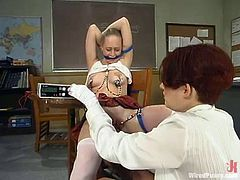 The blonde student is getting toyed and tortured with other kinky devices by her redhead teacher in this BDSM lesbian video.
