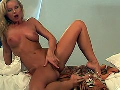 Naughty blonde MILF with nice tits poses for a camera lying on bed. She licks the fingers to make them wet and then start to shove them deep in her hot pussy.