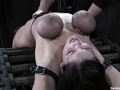 Kinky brunette girl lies on a bondage device being tied up. She gets her tits twisted so hard that they become purple. Her master also toys her pussy.