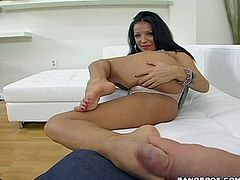 A slutty chick gets naked and pleasures a foot fetishist bastard by jerkin' him off with her feet till he blasts his load.