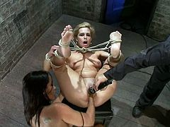 Naughty blonde girl lies on a wooden chest being tied up. Brunette girl fucks her with a strap-on and fists her pussy.