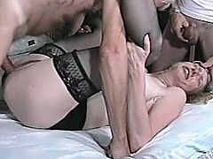 A skinny mature blonde is playing dirty games with two dudes in a bedroom. The guys mouth-fuck the skank and then drill her snatch in missionary and other positions by turns.