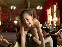 This Asian girl is a sex servant. She gets tied up and toyed while other people watch at her. After that she sucks big dicks and gets fucked hard on a table.