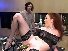 Salacious redhead milf Audrey Hollander wearing fishnet stockings is going crazy in the kitchen. She pokes a cucumber and a sausage into her asshole and then allows some dude to fuck her holes.