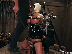 This petite siren gets latex mask and gets trapped in the bondage device. Then babe gets to suck her master's cock for something in contrast to pain!