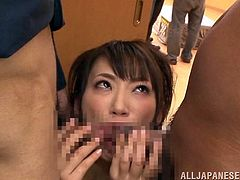 Saki Kouzai sucks two schlongs and enjoys a massive facial cumshot