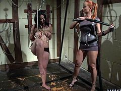 Vulgar black haired slave chick is all naked and bounded to the cross. Horny redhead mistress brutally squeezes her big tits and fucks her throat with big strapon.