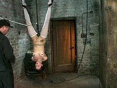 Cheerful brunette babe takes her dress off and then she gets hanged up upside down. She gets her tits tortured and pussy toyed with a vibrator.